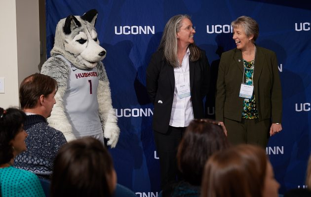 Jonathan the Husky, left,  Ellyssa Eror, Student Health Services, and Mary Ann Phaneuf, School of Pharmacy wait as President Herbst announces the winner of the Unsung Hero Award