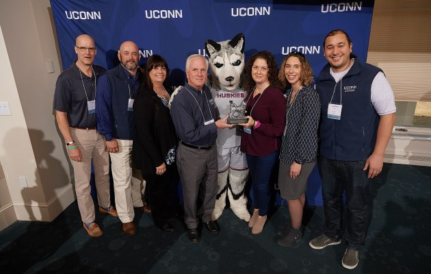 Team Award winners Veterans Affairs and Military Programs staff pose with Jonathan the Husky