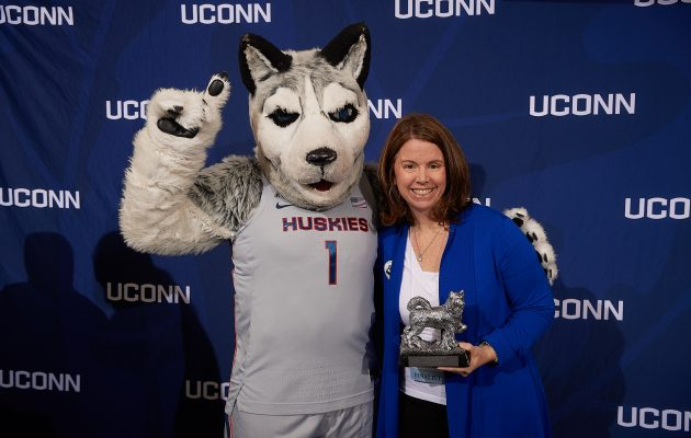 Cinnamon Adams of the Graduate School poses with Jonathan the Husky after receiving the University Citizen Award