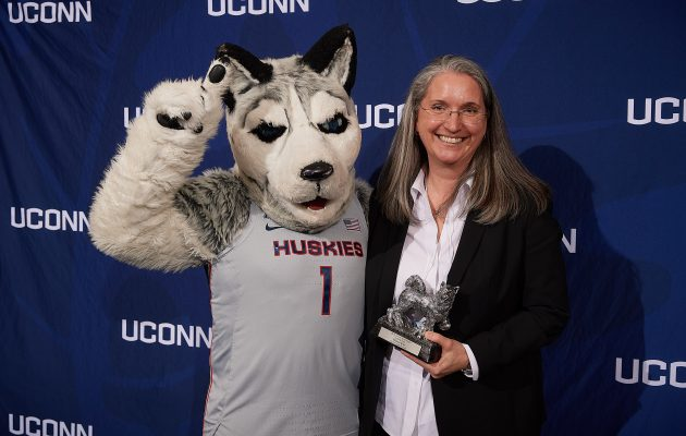 Ellyssa Eror, Student Health Services, poses with Jonathan the Husky after receiving the Unsung Hero Award